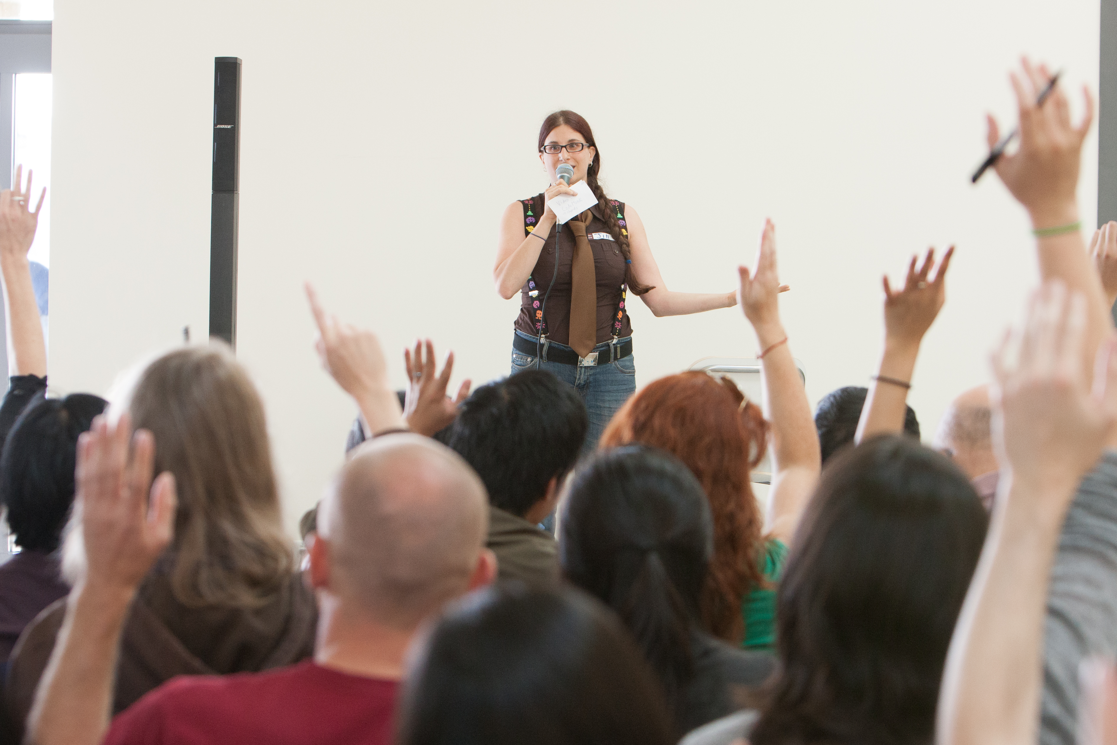 A woman holding a microphone, in front of a lot of people with raised hands.