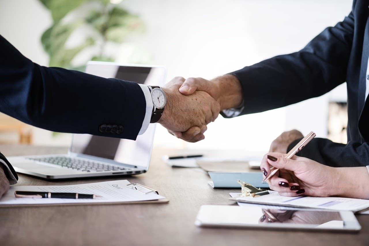 Two people in business attire shaking hands over an office desk.
